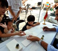Skilled hand: Tunisian Embassy Counselor Mohamed Trabelsi hands the name of Airi Yano, written in Arabic, to the 1-year-old's mother, Setsuko, 36, while 4-year-old brother Taisei looks on. | YOSHIAKI MIURA