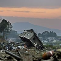 Out of the wreckage: A destroyed house sits among debris from the March 11 earthquake and tsunami in Kesennuma, Miyagi Prefecture, on Friday. Below: A family prays for the deceased at a memorial in Natori, Miyagi Prefecture, the same day. | KYODO PHOTOS