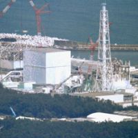 Desolation row: The buildings of the four troubled reactors at the Fukushima No. 1 plant are seen from the air in August. | KYODO PHOTO