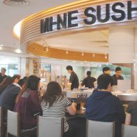 What comes around: People eat at a conveyor-belt sushi restaurant in Hong Kong in August. | KYODO