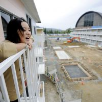 Room with a view: Elementary school fourth-grader Serina Hamada takes in the view from the balcony of a three-story temporary housing facility Sunday in Onagawa, Miyagi Prefecture. | KYODO PHOTO