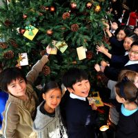 'Tis the season: Children from Nishimachi International School and another private school in Tokyo hang ornaments and cards on a Christmas tree at the Grand Hyatt Tokyo hotel in Minato Ward's Roppongi district Wednesday. | YOSHIAKI MIURA PHOTO