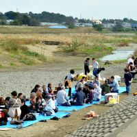 In good taste: A large group holds a barbecue Nov. 8 along the Tama River in the Futako-Shinchi district in Kawasaki, the only place the city officially permits such activities. | YOSHIAKI MIURA