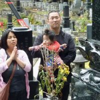 Etsuko Shimosawa prays while her husband, Hiroki, holds their daughter, Sakura, in front of the grave of Etsuko's mother, who was killed in the March 11 tsunami, in Miyako, Iwate Prefecture.