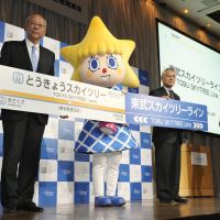 Reach for the sky: Tobu Tower Sky Tree Co. President Michiaki Suzuki (left), company mascot Sorakara-chan, and an unidentified Tobu Railway Co. executive hold name plates for the new Tokyo Skytree train line and station at a news conference in Tokyo on Feb. 9. | KYODO
