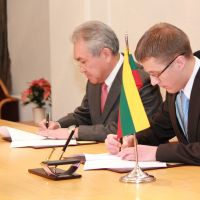 Nuclear partnership: Masaharu Hanyu, vice president and executive officer of Hitachi Ltd. (left), and Zygimantas Vaiciunas, head of Lithuania's concession tender commission and the vice minister of energy, sign a tentative concession treaty in December in the Baltic state. | HITACHI LTD.