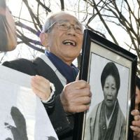In the picture: Akio Mizoguchi beams as he holds up a photo of his mother, Chie, who was posthumously recognized as a victim of the Minamata mercury poisoning Monday at the Fukuoka High Court. | KYODO
