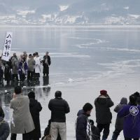 Back to the future: A priest from Yatsurugi Shrine conducts the 'omiwatari' ritual on Lake Suwa, Nagano Prefecture, on Feb. 6. | CHUNICHI SHIMBUN
