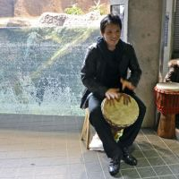 Gator aid: Percussionist Goshin Moro beats a drum by the alligator pen at Maruyama Zoo in Sapporo on Monday. | KYODO
