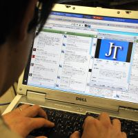 Connected: A person in Tokyo checks Twitter posts recently. The March 11 calamities proved social media are a powerful way to communicate during major emergencies. | YOSHIAKI MIURA
