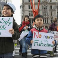Generation N: Fukushima Prefecture natives Yuri Tomitsuka, 10, and Kaisei Fukagawa, 7, who relocated to Yokohama and Tokyo after the nuclear crisis started, take part with their mothers in an antinuclear demonstration in New York on Thursday. | KYODO