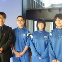 Shin Saito, a Kamaishi East English teacher, and third-year students (from left) Fumiya Akasaka, Aki Kawasaki and Kana Sasaki pose Feb. 20 at their temporary home, Kamaishi Junior High School.
