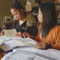 Care worthy: Charito Ito (left) works at home with fellow Filipino Cristina Konno in Kesennuma, Miyagi Prefecture, on Feb. 22 to finish the final report for their caregiver course. | SETSUKO KAMIYA