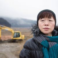 Searching for answers: Akemi Karino looks around the desolate landscape at Okawa Elementary School in Ishinomaki, Miyagi Prefecture, on Feb. 23. | ROB GILHOOLY