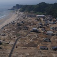 Eye in the sky: A photo shot by Eiji Sakai while paragliding in May 2008 shows Iwaki's once thriving community in Fukushima Prefecture. Below: A picture of the same area last July shows that virtually all that remains are empty lots. | EIJI SAKAI