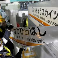 On the way up: Workers unveil a new sign at former Narihirabashi Station in Sumida Ward, Tokyo, on Saturday as the rail stop was renamed Tokyo Sky Tree Station. | KYODO