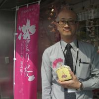 How sweet it is: Junya Tomita of the Fukushima Prefecture Tourism & Local Products Association holds a package of 'mama-doru' sweets at a Fukushima shop in Tokyo. | JUN HONGO
