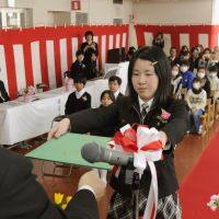 Onward and upward: A student from Tomioka No. 1 Elementary School who was displaced by the Fukushima nuclear crisis receives a graduation certificate Friday at a different school in Miharu, Fukushima Prefecture. | KYODO