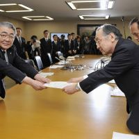 Message received: Yamanashi Gov. Masaaki Yokouchi (right) hands Tokyo Electric Power Co. President Toshio Nishizawa a request regarding the utility's planned electricity rate hike at a meeting Wednesday in Tokyo. | KYODO