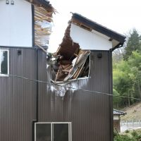 Hole in one: A residence in Komatsu, Ishikawa Prefecture, shows the damage from a tree that was knocked down by Tuesday's storm.   KYODO