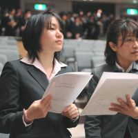 Barrier-free education: Misato Fujiwara (left), assisted by a sign-language interpreter, attends her graduation ceremony March 15 in Nagoya after earning a license to teach English. | CHUNICHI SHIMBUN