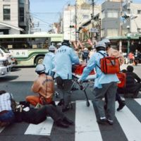 First responders: Paramedics help people injured by a rampaging minivan at a busy intersection in the historic Gion district in Higashiyama Ward, Kyoto, on Thursday. | KYODO