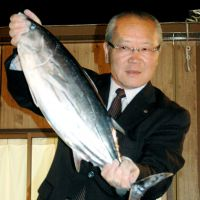 Vote catcher: Mayor Shigeo Ishihara of Omaezaki, Shizuoka Prefecture, holds up a bonito, one of the city's chief products, Sunday night after winning his third term as mayor.   KYODO