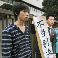 Rejected: Zhou Tong (left) stands outside the Tokyo District Court on Monday after it threw out a damages suit he and another Chinese filed over injuries caused by a gas shell left behind by Japan after World War II. | KYODO