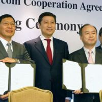 Softbank leader Masayoshi Son (second from right) displays a joint accord signed March 12 in Tokyo to set up a firm to explore renewable energy in Mongolia, with the country's prime minister, Sukhbaataryn Batbold, (second from left) looking on. | KYODO