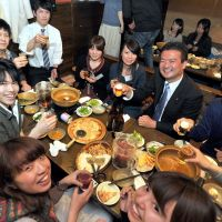 Booze talking?: Democratic Party of Japan member Keisuke Tsumura (second from right) mingles with students Wednesday during a 'nomikai' event at a pub in Tokyo to counter youth apathy toward politics and boost voter turnout. | YOSHIAKI MIURA