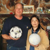 Return to sender: Alaska residents David and Yumi Baxter hold a soccer ball and a volleyball bearing Japanese characters that washed up on a beach on Middleton Island in March. | KYODO