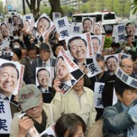 Comeback trail: Supporters of Ichiro Ozawa hold up photos of the ex-Democratic Party of Japan president and notes reading 'Innocent' at the Tokyo District Court on April 26. | KYODO