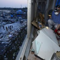 Out of nowhere: A resident clears debris from his apartment Monday after a tornado ripped through the building and many other nearby homes the day before in Tsukuba, Ibaraki Prefecture. | KYODO