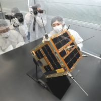Thaw watcher: A Weathernews Inc. employee shows off a micro satellite for monitoring Arctic Ocean ice conditions during a media preview Tuesday in the city of Chiba. | YOSHIAKI MIURA PHOTO