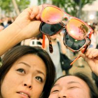Stellar performance: Time-lapse photography captures Monday's annular eclipse in Tokyo. Students of Honmura Elementary school (bottom) in Minato Ward share the moment, as women in the Odaiba waterfront (below) try to see it through their sunglasses after proper glasses were all sold out. | AFP-JIJI, YOSHIAKI MIURA, MADS BERTHELSEN