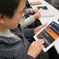 Hands on: A man is shown how to operate the zoom function on an iPad during a study group for the visually impaired in Chiyoda Ward, Tokyo, in February. | KYODO
