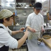 Tool of the trade: Kazuko Kishikawa, an employee of the Oirantan curry restaurant in Takeo, Saga Prefecture, takes a picture of curry at the restaurant last month to post on the city's Facebook page. | KYODO