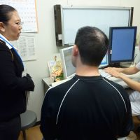 Communicating aid: A medical interpreter helps a Brazilian man of Japanese descent communicate with a Japanese doctor at a hospital in Toyota, Aichi Prefecture, in November. | KYODO