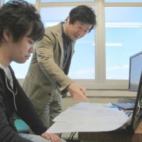 Hideo Izumida (right) and a student at Toyohashi University of Technology in Aichi Prefecture check sketches ahead of work to renovate damaged cultural assets in Kesennuma, Miyagi Prefecture. | CHUNICHI SHIMBUN