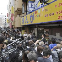 End of story: The media converge on a manga cafe where Aum Shinrikyo fugitive Katsuya Takahashi was seized by Tokyo police Friday morning, after 17 years on the run. Below: Takahashi is transferred to Metropolitan Police Department headquarters.   KYODO PHOTOS