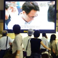 Gotcha: Passersby view a large television screen around noon Friday near Hankyu Umeda Station in Osaka as news unfolds about the arrest of Aum fugitive Katsuya Takahashi.