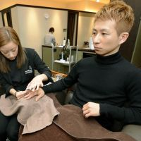 A 34-year-old patissier has his nails done at a men's beauty salon in Osaka on March 29.   KYODO