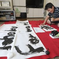 Brushing up: Takuya Takahashi practices calligraphy at his home in Morioka, Iwate Prefecture, on Sunday. His work, 'Tohoku Forward,' is on display at a site for an upcoming U.N. conference in Rio de Janeiro. | KYODO