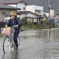 Pedal or paddle?: A woman bicycles Wednesday on a street flooded by Typhoon Guchol the previous day in Ishinomaki, Miyagi Prefecture. | KYODO