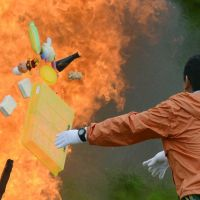 Sacrificial bonfire: A man throws toys into a fire during a memorial service Sunday at Okawa Elementary School in Ishinomaki, Miyagi Prefecture, which was devastated by the March 11, 2011, tsunami. | KYODO