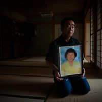 Incalculable loss: Mikio Watanabe holds a photograph of his wife, Hamako, on Monday. He blames Tokyo Electric Power Co. for her suicide and is seeking compensation from the utility. | THE WASHINGTON POST