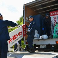 Accessible: Police pack up 'no entry' signs in Naraha near the crippled Fukushima No. 1 nuclear plant before the town's no-go zone status was lifted at midnight Thursday. | KYODO