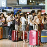 Travelers wait to check-in at Narita International Airport the same day. | KYODO PHOTOS