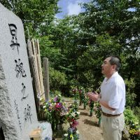 In memory: Masaru Onishi, chairman of Japan Airline Corp., prays Sunday at a memorial to the 520 victims of the jet that crashed into Osutaka Ridge in Gunma Prefecture in 1985. | KYODO