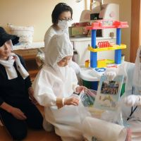 Home sweet home: Daughters of nuclear evacuee Hiromi Konno (rear) pack items in a bag Friday in Naraha, Fukushima Prefecture, when they temporarily returned to the town. | KYODO